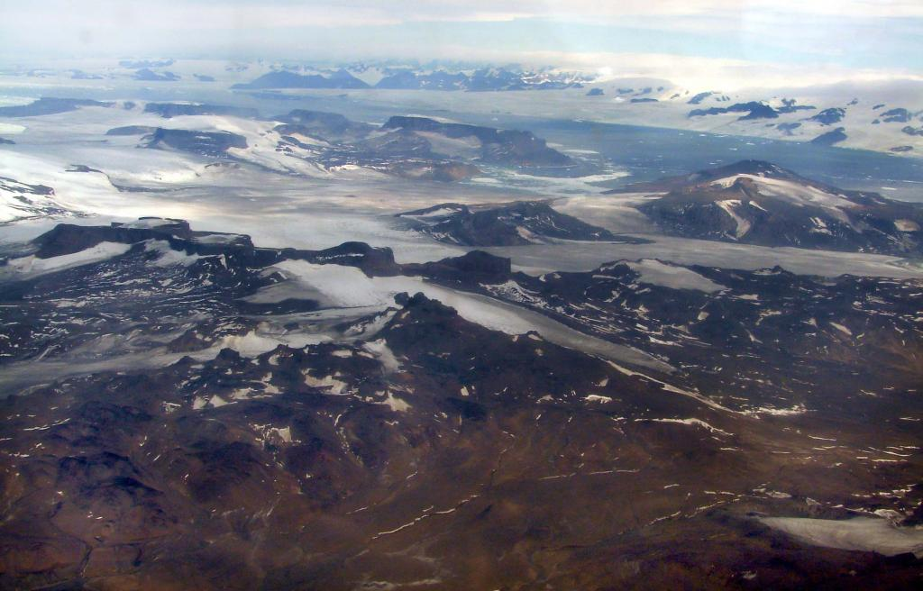 "This in-flight photo shows James Ross Island (foreground) and the Antarctic coastline, including Victory Glacier (background). Photo Credit: Courtesy Ted Scambos and Rob Bauer, NSIDC  <a href=""http://nsidc.org/icetrek"">IceTrek Web site</a> (<a href=""/cryosphere/gallery/photo/32913"">View photo detail.</a>) <br>"
