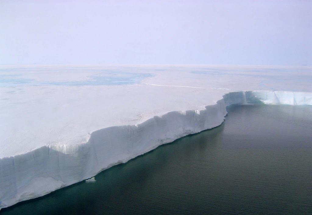 "This in-flight photo shows the edge of the Larsen B Ice Shelf. The surface is melted, and ice flows off the edge like a waterfall. Photo Credit: Courtesy Ted Scambos and Rob Bauer, NSIDC  <a href=""http://nsidc.org/icetrek"">IceTrek Web site</a> (<a href=""/cryosphere/gallery/photo/32912"">View photo detail.</a>) <br>"