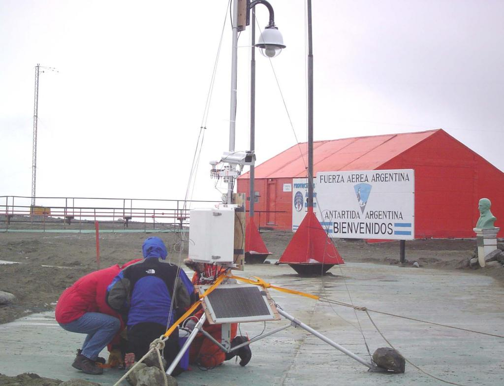 "The crew sets up the weather tripod (the smaller of the two weather stations) outside Marambio Station to run some final tests before they deploy it on AMIGOSberg. Photo Credit: Courtesy Ted Scambos and Rob Bauer, NSIDC  <a href=""http://nsidc.org/icetrek"">IceTrek Web site</a> (<a href=""/cryosphere/gallery/photo/33347"">View photo detail.</a>) <br>"