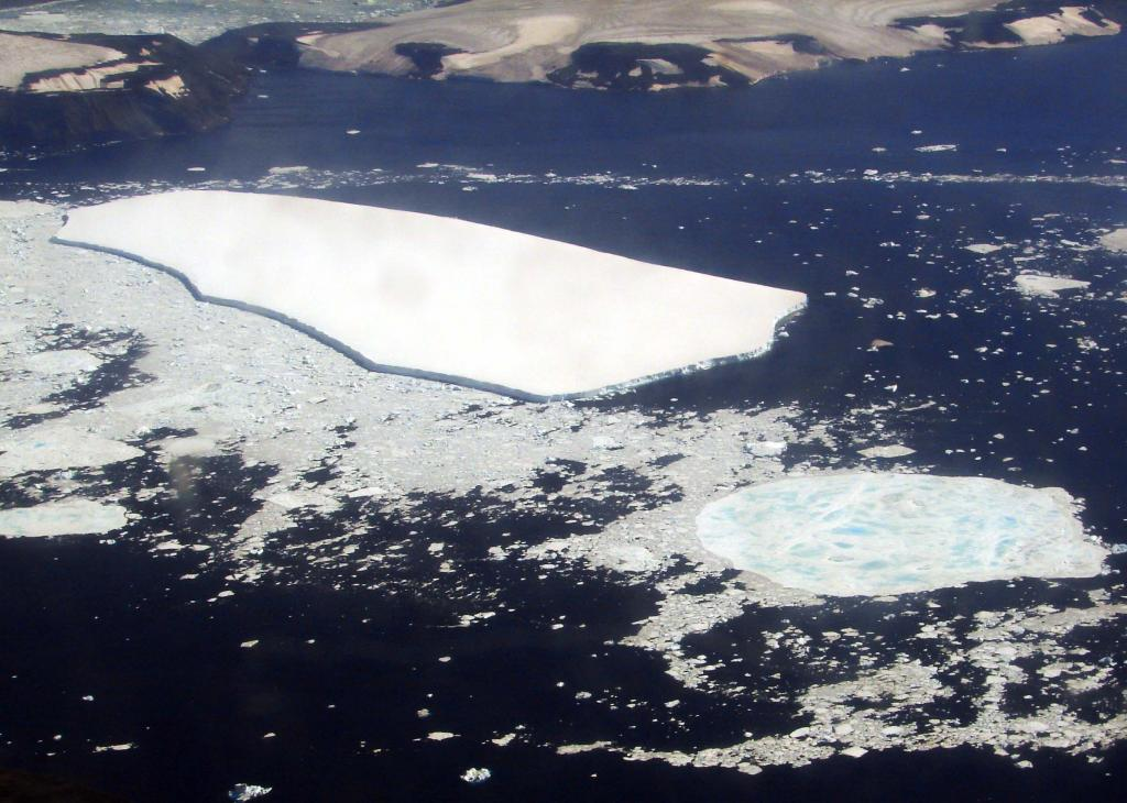 "This in-flight photo shows Vegaberg with Vega Island in the background. Photo Credit: Courtesy Ted Scambos and Rob Bauer, NSIDC  <a href=""http://nsidc.org/icetrek"">IceTrek Web site</a> (<a href=""/cryosphere/gallery/photo/32949"">View photo detail.</a>) <br>"