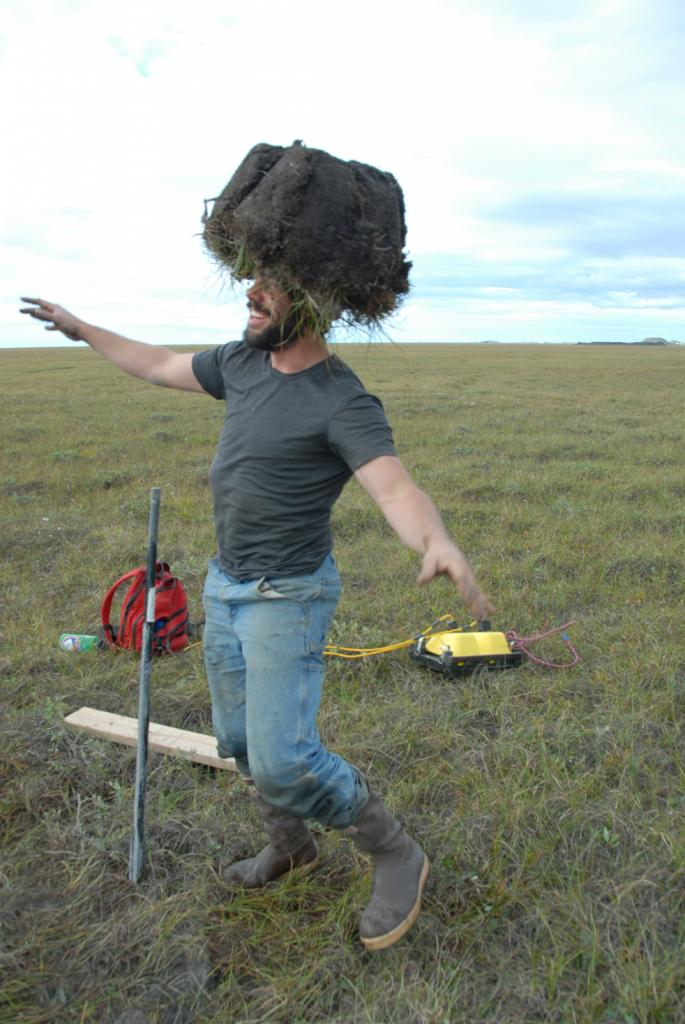 "Alessio Gusmeroli models his new turf top hat after drilling a permafrost core near Deadhorse, Alaska on August 17, 2012). (Credit: Tingjun Zhang, NSIDC) (<a href=""/cryosphere/gallery/photo/34176"">View photo detail.</a>) <br>"