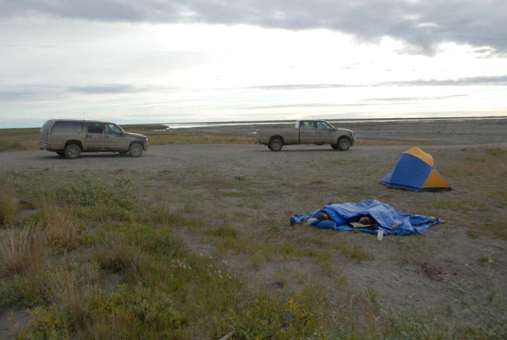 "Dawn finds Kevin Schaefer and Tim Schaefer still sleeping at camp near the Sagavanirktok River south of Deadhorse, Alaska on August 16, 2012. Mud makes the trucks appear brown, although their true colors are red and blue (Credit: Tingjun Zhang, NSIDC). (<a href=""/cryosphere/gallery/photo/34178"">View photo detail.</a>) <br>"