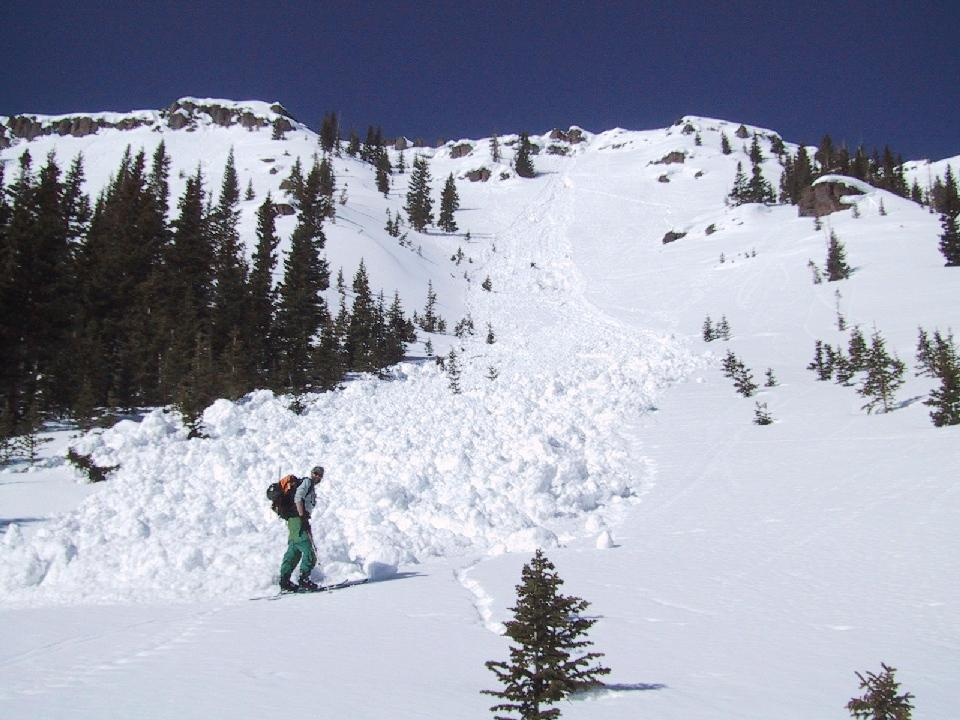"John Saunders standing beneath avalanche debris. In Trappers Lake area in the Flat Tops Mountains, near Steamboat Springs, Colorado. Image Credit:  Courtesy Lynn French, NSIDC. (<a href=""/cryosphere/gallery/photo/33396"">View photo detail.</a>) <br>"