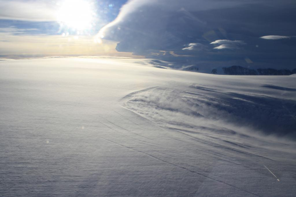 "Cold winds blowing snow into the Crane Glacier drainage basin during the LARISSA 2013 Project. Above are standing wave lenticular clouds, similar to those seen in Colorado's Front Range.  The Larsen Ice Shelf System, Antarctica (LARISSA) Project is a large, interdisciplinary, multi-institute study to explore every aspect of the deteriorating Larsen Ice Shelf region in Antarctica. Participating researchers set up instruments on the glaciers that feed into the remaining portion of the Larsen ice shelf. As changes occur on the ice, the stations will record it in data and pictures. (Credit: Ted Scambos, NSIDC) Read the expedition blog on <a href=""http://iceshelf.wordpress.com"">http://iceshelf.wordpress.com</a>. (<a href=""/cryosphere/gallery/photo/34129"">View photo detail.</a>) <br>"